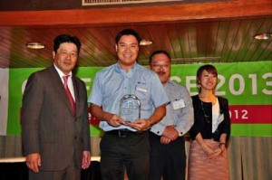 Fiesta Resort & Spa Saipan resident manager Abner Acosta receives the Rakuten Travel Diamond Award for 2013 from Rakuten Travel President Masashi Okatake,  accompanied by Fiesta Resort Sales & Marketing director Junichi Mitagawa and Ayano Ueda from Sales in the Japan Office. (Photo courtesy of Saipan Tribune)
