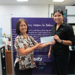 Florida Alba, Fiesta Assistant Human Resources Manager, presents $550 check to a representative of the American Cancer Society in